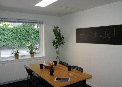 Udsyn fra møderummet i kontorlokale 32 til gården med de grønne planter